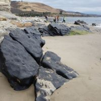 Oiled boulders on a California beach with cleanup workers in the distance.
