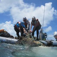 Scientists load onto a small boat marine debris collected at Midway Atoll.