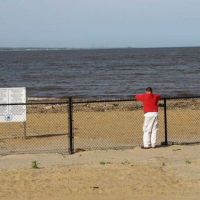 Person standing at a fenced-off beach closed to the public.