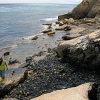 Cleanup worker and oiled boulders where the oil entered the beach.