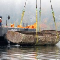 Workers direct the lifting of a rusted boat from a waterway onto a barge.
