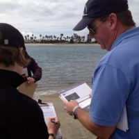 Two people looking at forms and a booklet on the beach.