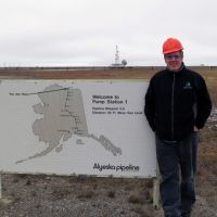 Man in hard hat outside at sign at start of Trans Alaska Pipeline.