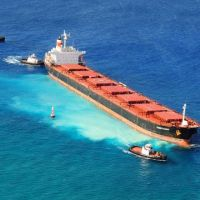 Surrounded by response vessels, the cargo ship VogeTrader grounded on coral.