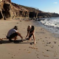Two men picking up objects from beach. Image credit NPS.