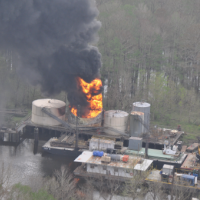 Fire burns in one of several oil tanks on a platform in a bayou.