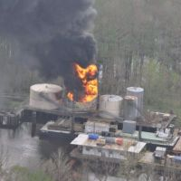 Flames and dark smoke billow from oil production platform fire next to a bayou.