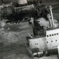 Black and white photo of ship sinking in ocean.