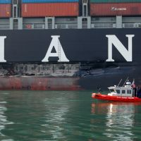 US Coast Guard skiff examines damaged side of M/V Cosco Busan.