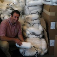 A person posing in front of a pile of bundles.