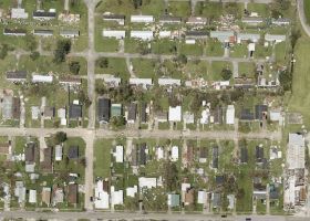 Aerial image of a housing area with hurricane damage and debris.