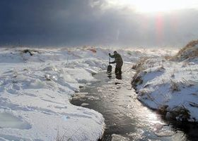 Person working in a stream in a frozen environment.