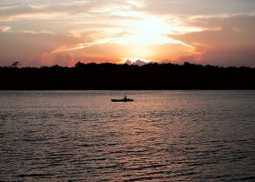 A kayaker on the water at sunset.