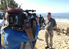 A camera crew filming a man on a beach.