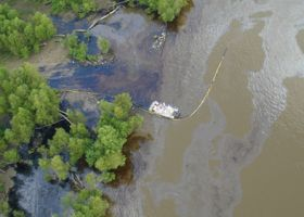 Aerial view of an oil spill in a river.