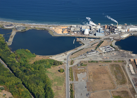 Aerial view of land, facility, and surrounding water.
