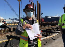Woman in safety vest gesturing to a paper in her hand.