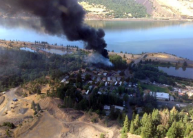 Aerial view of black smoke coming from near a body of water.