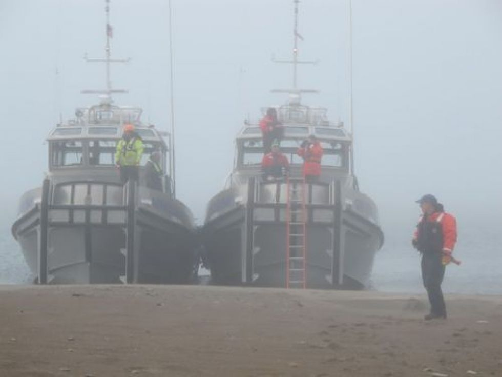 Two boats in fog with man on beach. Image: NOAA.