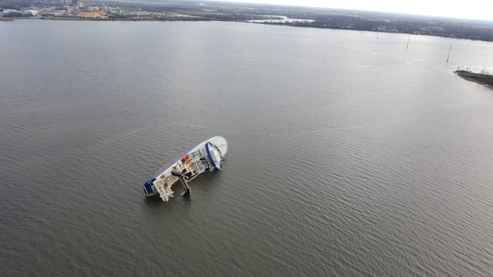 An aerial view of a vessel on its side in a body of water.