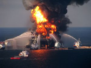 Several vessels pumping pressurized water on an oil rig on fire.