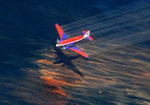 An aircraft releases chemical dispersant over an oil slick.