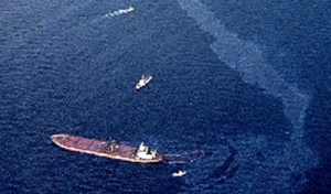 An aerial view of an oil sheen in water next to a vessel.