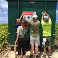 A group of people putting a sign on a large bin.