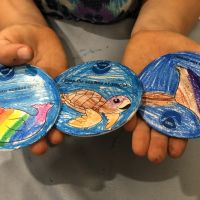Hands holding three painted plates.