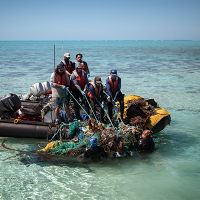 Group in a small boat hauling tangled nets and debris from the water.
