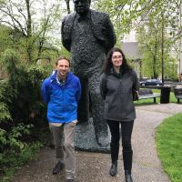 Two people posing for photo in front of a statue.