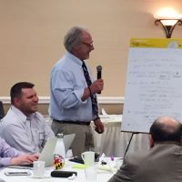 Man teaching class, looking at flip chart