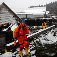A woman in response gear with a collapsed structure behind her.