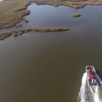 Aerial view of a boat heading towards a marsh.