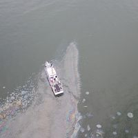 Aerial view of vessel on water in oil slick.
