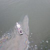 Aerial view of vessel on water in oil slick.
