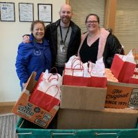 Three people posing with boxes of gift bags.