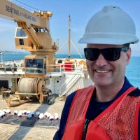 A man in a hard hat and an orange vest with large equipment and a shoreline in the background.