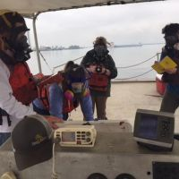 People in pollution masks on a boat.