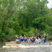 Group of people in a boat on a river.