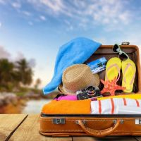 Suitcase with flip-flops, sunglasses, hat, etc.