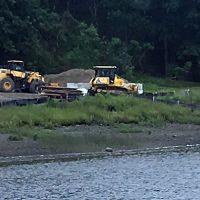 Heavy equipment operating on a riverbank.