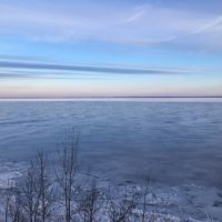 Large body of water the is frozen near the shore.