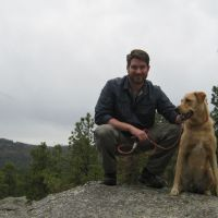 Man and dog sitting on a rock outdoors.