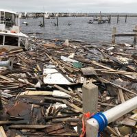 A vessel and a large pile of marine debris in the water next to a dock.