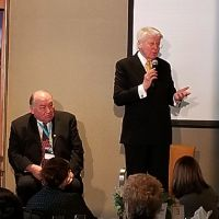 Two men at front of room addressing a group.