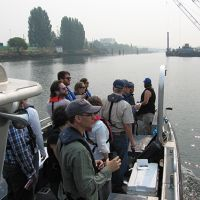 Group of people on a boat deck on a river.