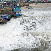 An aerial view of a roller coaster, wrecked, in the ocean.
