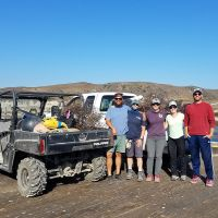 Group of five people pose next to small vehicle with debris in the back.