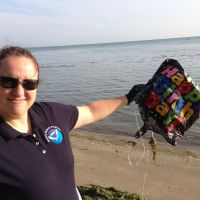 "A woman on a beach holding a deflated ""Happy Birthday"" balloon."